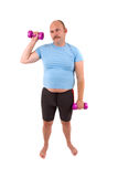 Hating sports. Demotivated sports man with dumbbells and a too tight shirt stock image
