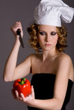 Hating vegetables. Woman with chefs hat trying to stab a pepper Stock Images