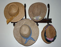Hats 1. Straw hats hanging on wooden coat rack Royalty Free Stock Photos