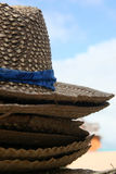 Hats. Straw hats stacked up with beach and sky in background Stock Image
