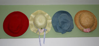 Hats. Little girl's hats, hanging on a wall royalty free stock photo