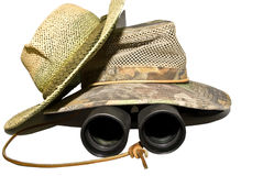 Hats and Binoculars. Two mesh safari style, summer hats  with binoculars underneath.  Search out the details or information you need to stay ahead in business Royalty Free Stock Image
