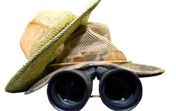 Hats and Binoculars. Two mesh safari style, summer hats  with binoculars underneath.  Search out the details or information you need to stay ahead in business Royalty Free Stock Photo