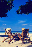 Hats on chairs of tropical beach Stock Image