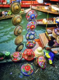 Hats, Floating Market, Thailand. A little boy eats lunch next to a colorful straw hat display at a local floating market near Bangkok, Thailand Royalty Free Stock Photography