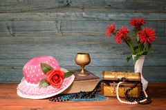 Hats, jewelry and flowers in a vase Royalty Free Stock Photo