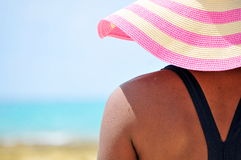 Hats off to Summer. Young woman at tropical beach wearing pink and tan straw hat looks toward the sea Royalty Free Stock Photos