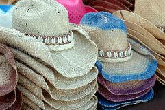 Woven Straw Cowboy Hats with Shells. Stacks of woven straw cowboy style hats with shell hat bands at outdoor market Stock Image