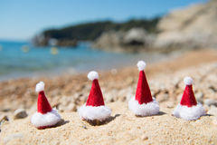 Hats of Santa Claus at the beach. Row hats of Santa Claus at the summer beach royalty free stock photos
