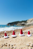 Hats of Santa Claus at the beach Royalty Free Stock Images