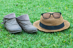 Hats shoes glasses on grass at park. Royalty Free Stock Images