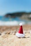Hatt av Santa Claus på stranden Royaltyfri Foto