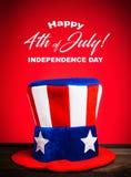 Hatt för farbror Sam på röd bakgrund med den lyckliga Juli 4th hälsningen Arkivfoto