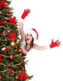 hatt för julflickahand nära den santa treen upp Arkivbilder