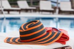 Hatt och handduk på sunbed arkivbild