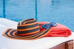 Hatt och handduk på sunbed royaltyfri bild