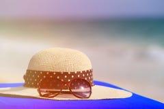 Hatt och solglasögon på den tropiska stranden Fotografering för Bildbyråer