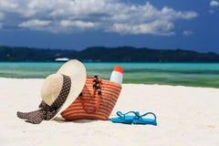 Hatt, påse, solexponeringsglas och flipmisslyckanden på den tropiska stranden Royaltyfri Bild