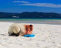 Hatt, påse, solexponeringsglas och flipmisslyckanden på den tropiska stranden Arkivbild