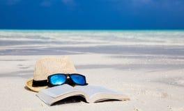 Hatt, solglasögon och en bok på stranden Fotografering för Bildbyråer