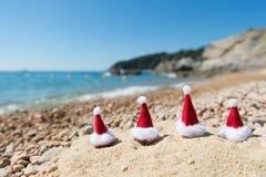 Hattar av Santa Claus på stranden Royaltyfri Fotografi