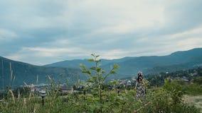 Hatten och klänningen för ung brunettkvinna är den bärande att gå som är utomhus- under sommardag blå himmel med moln och berg på stock video