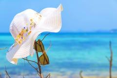 Hatten och solglasögon på tropisk sand sätter på land solglasögon på stranden Den härliga havssiktstapeten, bakgrund tyckte om en Royaltyfria Bilder