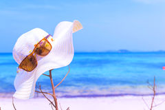 Hatten och solglasögon på tropisk sand sätter på land solglasögon på stranden Den härliga havssiktstapeten, bakgrund tyckte om en Royaltyfri Foto
