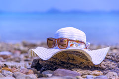 Hatten och Sunglass timrar på stranden kopplar av det tonade begreppet för ferie för sommarsemestern Arkivfoto