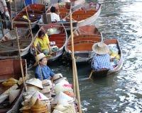 Hattsäljare som sitter på hennes fartyg och många fartyg i kanalen på Damnoen Saduak som svävar marknaden royaltyfria bilder