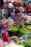 Lady examines vegetables as fresh food market bazaar  in Hatyai Thailand. Hatyai, Thailand - May 6, 2017: A Thai lady examines some fresh green bean vegetables Stock Photography