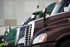 Hauben drei halb LKWs, die auf Fernfahrerrastplatz stehen Lizenzfreie Stockfotografie