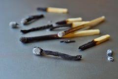 Haufen des gebrannten Matches und der Asche auf dem silbernen Hintergrund als Symbol der Abführung, der Entleerung und der Zerstö stockfotos