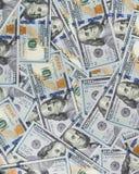 Haufen des Geldes in hundert Dollarbanknoten verbreitete auf Oberfläche Stockfotos