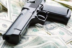 Haufen des Geldes und der Pistole Lizenzfreie Stockfotos