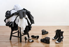 Haufen des Kleidens auf einem Schemel und zerrütteten Schuhen lizenzfreies stockbild