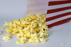 Haufen des Popcorns vom Kasten des roten und Weißbuches auf dem weißen Boden stockfotografie
