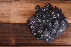 Haufen des schwarzen Papiers mit FRAGEZEICHEN auf Holztisch Stockbild