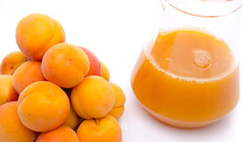Haufen von Aprikosen und von Krug Aprikosensaft Lizenzfreie Stockfotografie