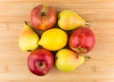 Haufen von Birnen, von Äpfeln und von Zitrone auf Bambusbrett Stockbilder