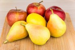 Haufen von Birnen, von Äpfeln und von Zitrone an Bord Lizenzfreies Stockbild
