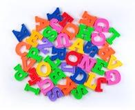 Haufen von bunten Alphabetplastikbuchstaben auf einem Weiß Stockbild