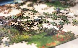 Haufen von bunten Puzzlespielelementen auf beige Oberfläche Lizenzfreie Stockfotos