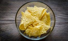 Haufen von Corn chipen in der Glasschüssel auf dem hölzernen Hintergrund Lizenzfreie Stockbilder
