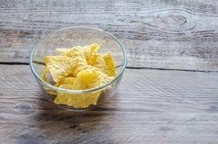 Haufen von Corn chipen in der Glasschüssel auf dem hölzernen Hintergrund Stockfoto