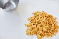 Haufen von Corn-Flakes auf einem gemalten weißen hölzernen Hintergrund Corn-Flakes zerstreut auf einen Holztisch lizenzfreie stockfotos