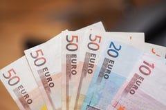 Haufen von Eurobanknoten auf einem Holztisch Stockbilder