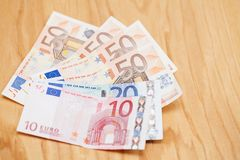 Haufen von Eurobanknoten auf einem Holztisch Stockbild