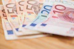 Haufen von Eurobanknoten auf einem Holztisch Lizenzfreies Stockfoto