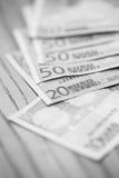 Haufen von Eurobanknoten auf einem Holztisch Stockfoto